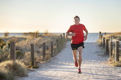Young attractive and happy sport runner man with fit and strong healthy body training on off road track in Summer running workout royalty free stock photography
