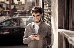 Young attractive happy stylish man on smart phone social network app in european city outdoors. Fashion college man in his twenties happy checking blog or stock photo