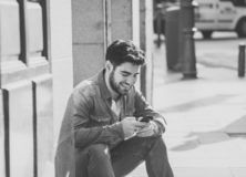 Young attractive happy stylish man on smart phone social network app in european city outdoors. Fashion college man in his twenties happy checking blog or stock images
