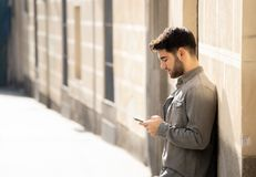 Young attractive happy stylish man on smart phone social network app in european city outdoors. Fashion college man in his twenties happy checking blog or stock image