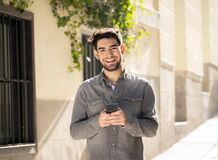 Young attractive happy stylish man on smart phone social network app in european city outdoors. Fashion college man in his twenties happy checking blog or royalty free stock photos