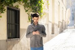 Young attractive happy stylish man on smart phone social network app in european city outdoors. Fashion college man in his twenties happy checking blog or royalty free stock photo