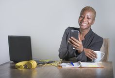 Young attractive and happy successful black afro american woman in business jacket working cheerful at office laptop using mobile royalty free stock photography
