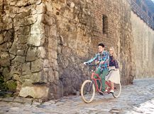 Young tourist couple, handsome man and pretty blond woman riding tandem bicycle along city street. Young attractive happy tourist couple in casual clothing stock photos