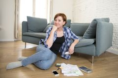 Young attractive and happy woman banking and accounting home mon. Thly cost and credit card expenses relaxed on living room floor doing paperwork smiling in royalty free stock image