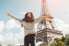 Young attractive happy woman jumping for joy against Eiffel Tower in Paris, France royalty free stock images