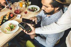 Young attractive Hindu man making a contactless smartphone payment stock photography