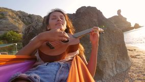 Young attractive hippie mixed race girl swinging in a hammock and playing ukulele guitar on the beach. Hd slowmotion