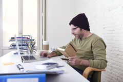 Young attractive hipster businessman working from his home office as freelancer self employed business model Royalty Free Stock Images