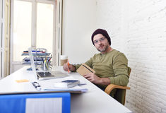 Young attractive hipster businessman working from his home office as freelancer self employed business model. Young happy hipster businessman working from his Royalty Free Stock Image