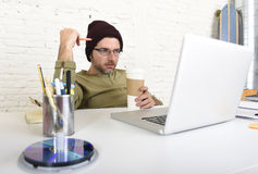 Young attractive hipster businessman working from his home office as freelancer self employed business model Royalty Free Stock Photo