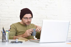 Young attractive hipster businessman working from his home office as freelancer self employed business model Stock Images