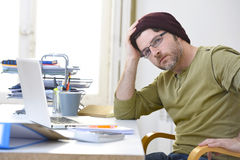 Young attractive hipster businessman working from home office as freelancer self employed business model Royalty Free Stock Image