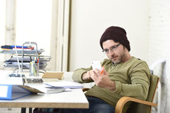 Young attractive hipster businessman working from home office with mobile phone Stock Photo