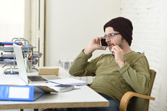 Young attractive hipster businessman working from home office with mobile phone Stock Photography