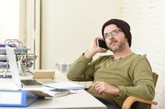 Young attractive hipster businessman working from home office with mobile phone Royalty Free Stock Photography