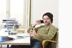 Young attractive hipster businessman working from home office with mobile phone Stock Image