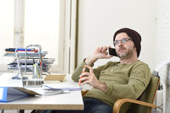 Young attractive hipster businessman working from home office with mobile phone Stock Photos