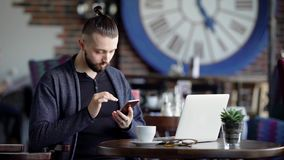 A young attractive hipster in a cafe, with a modern interior. A man is sitting at a table with coffee, using a. Smartphone, next to his laptop. Apparently there stock footage