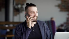 A young attractive hipster in a cafe, with a modern interior. A man is talking on the phone with a friend or colleague stock video footage
