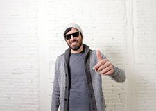 Young attractive hipster and trendy style looking man posing coo. Young attractive hipster and trendy style looking man smiling happy posing cool with attitude Stock Photos