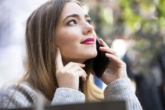 Young and attractive hipster woman is talking on her mobile with a face full of emotions. Royalty Free Stock Images