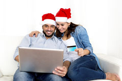 Young attractive Hispanic couple in love online Christmas shopping with computer Stock Photos