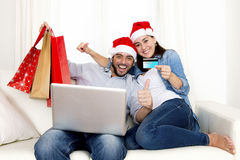 Young attractive Hispanic couple in love online Christmas shopping with computer Royalty Free Stock Photo