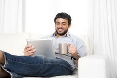 Young attractive Hispanic man at home on white couch using digital tablet or pad Stock Photography
