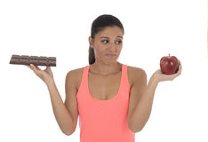 Young attractive hispanic woman in fitness top holding apple fruit and chocolate bar in her hands. In diet dilemma sweet tasty unhealthy food against healthy Royalty Free Stock Photography