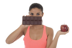 Young attractive hispanic woman in fitness top holding apple fruit and chocolate bar in her hands. In diet dilemma sweet tasty unhealthy food against healthy Stock Photos
