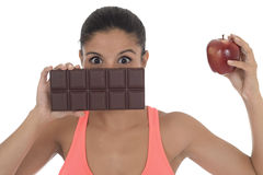 Young attractive hispanic woman in fitness top holding apple fruit and chocolate bar in her hands. In diet dilemma sweet tasty unhealthy food against healthy Royalty Free Stock Photos