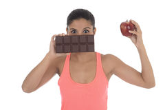 Young attractive hispanic woman in fitness top holding apple fruit and chocolate bar in her hands. In diet dilemma sweet tasty unhealthy food against healthy Stock Photo