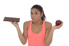 Young attractive hispanic woman in fitness top holding apple fruit and chocolate bar in her hands Stock Image
