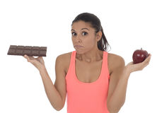 Young attractive hispanic woman in fitness top holding apple fruit and chocolate bar in her hands. In diet dilemma sweet tasty unhealthy food against healthy Stock Photography