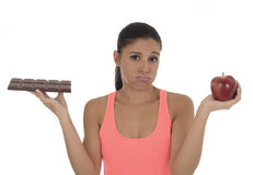 Young attractive hispanic woman in fitness top holding apple fruit and chocolate bar in her hands. In diet dilemma sweet tasty unhealthy food against healthy Stock Images