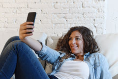 Young attractive hispanic woman lying on home couch taking selfie photo with mobile phone having fun Stock Photo