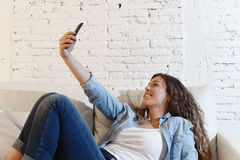 Young attractive hispanic woman lying on home couch taking selfie photo with mobile phone having fun Royalty Free Stock Photos