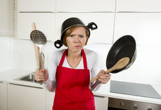 Young attractive home cook woman in red apron at kitchen holding pan and household with pot on her head in stress. Frustrated face expression in rookie amateur royalty free stock photography