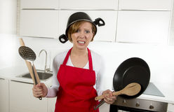 Young attractive home cook woman in red apron at kitchen holding pan and household with pot on her head in stress. Frustrated face expression in rookie amateur stock photo