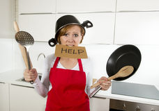 Young attractive home cook woman in red apron at  kitchen holding pan and household with pot on her head in stress Royalty Free Stock Image