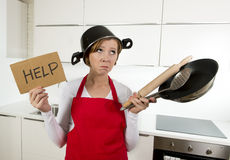 Young attractive home cook woman in red apron at kitchen holding pan and household with pot on her head in stress. Frustrated face expression in rookie amateur stock photos