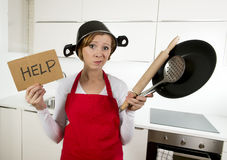 Young attractive home cook woman in red apron at kitchen holding pan and household with pot on her head in stress. Frustrated face expression in rookie amateur royalty free stock photos