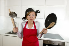 Young attractive home cook woman in red apron at  kitchen holding pan and household with pot on her head in stress Stock Photos
