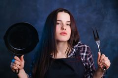 Young attractive housewife with frying pan and grill fork. ulin Royalty Free Stock Images