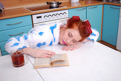 The young attractive housewife has fallen asleep at a kitchen table reading the book Royalty Free Stock Images