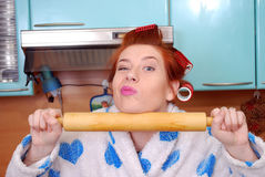The young attractive housewife in kitchen about hair curlers and keeps a rolling pin in a dressing gown Royalty Free Stock Images