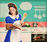 Young attractive housewife overlooked roast chicken in an oven Royalty Free Stock Images