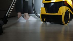 Young attractive housewife vacuuming in the room. Women use vacuum cleaner to cleaning the floor in living room at home during end of year clean. Housework stock video footage