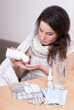 Young attractive ill woman taking pills in her living room Stock Images